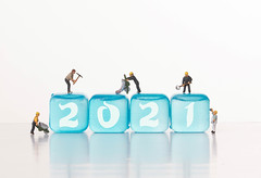 Workers on blue ice cubes with 2021 text