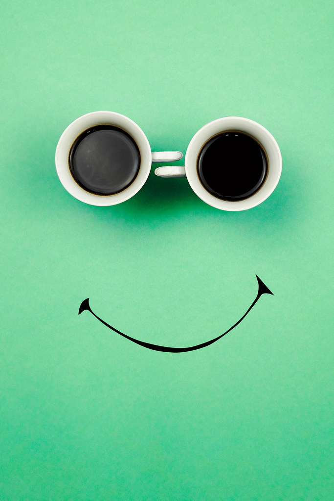 Two coffee cups with a smiling face