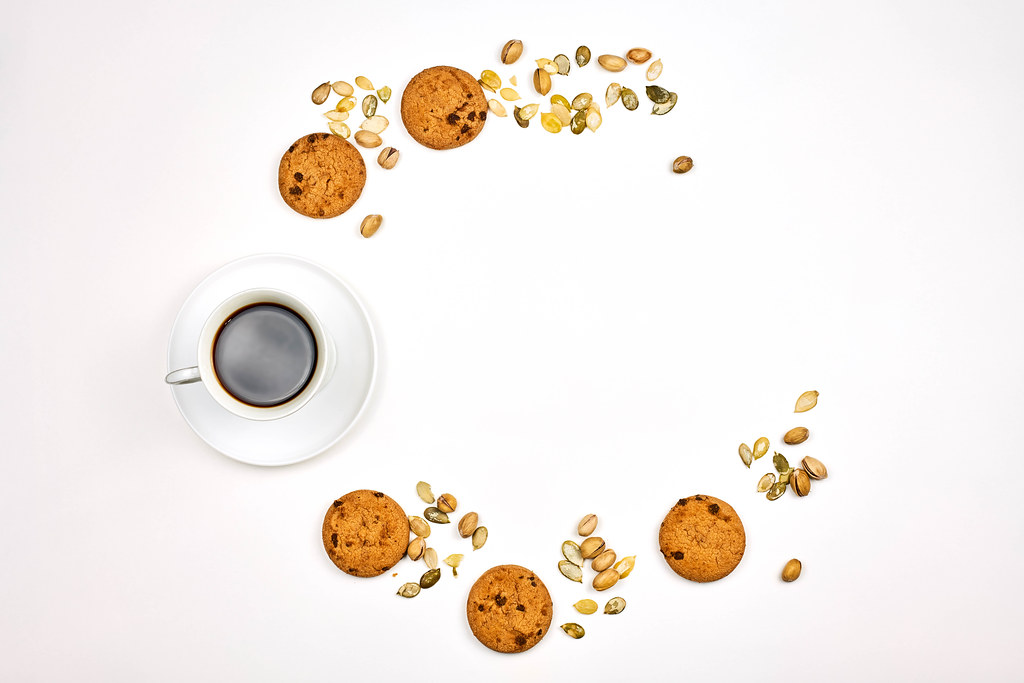 Black coffee, sweet oatmeal cookies, and different nuts forming a half-circle on white