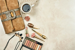 Female bag, different feminine cosmetics tools and cup of coffee