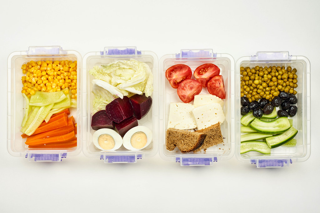 Catering service preparing and packing healthy vegetarian food in lunchboxes