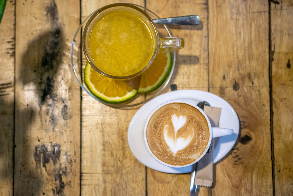 Top View Photo of Cup of Hot Cinnamon-Orange Tea and Cup of Cappuccino on a Wooden Table