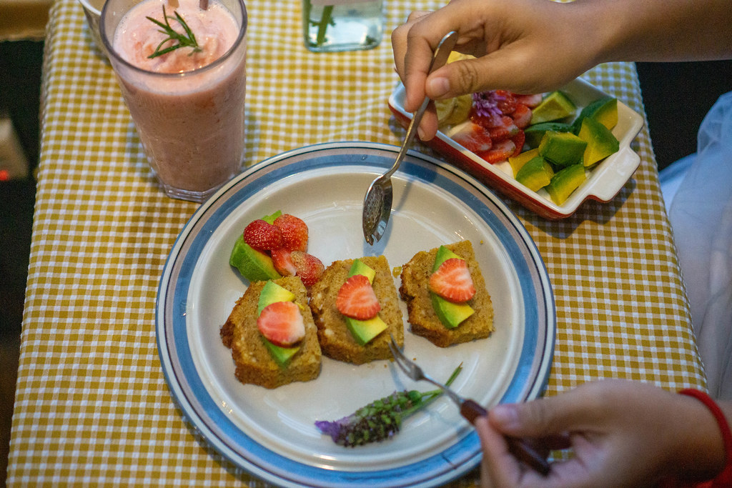 Person is eating Carrot Cake with Strawberries and Avocado with Spoon and Fork Top View