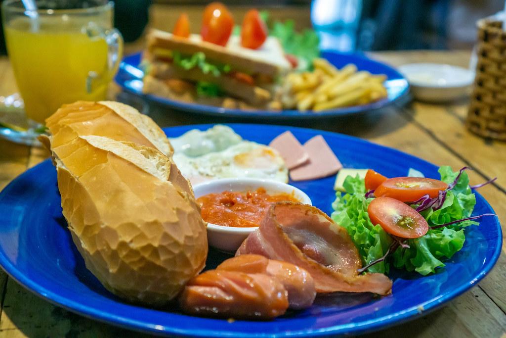 Baguette mit Wurst, Speck, Butter und Bohnen als Frühstück Nahaufnahme