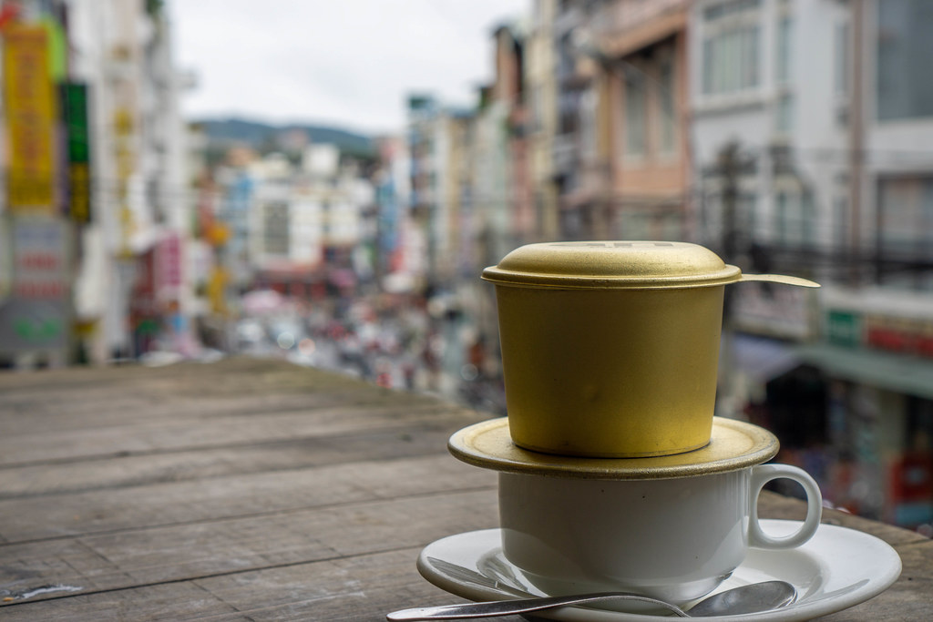 White Cup with Spoon, Saucer and Vietnamese Coffee Filter with City View in the Background