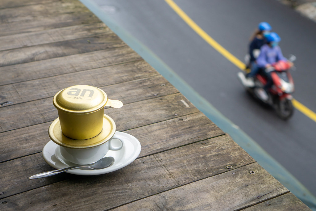 Bokeh Photo of Vietnamese Hot Coffee on a Wooden Table with a Motorbike driving past on the Street