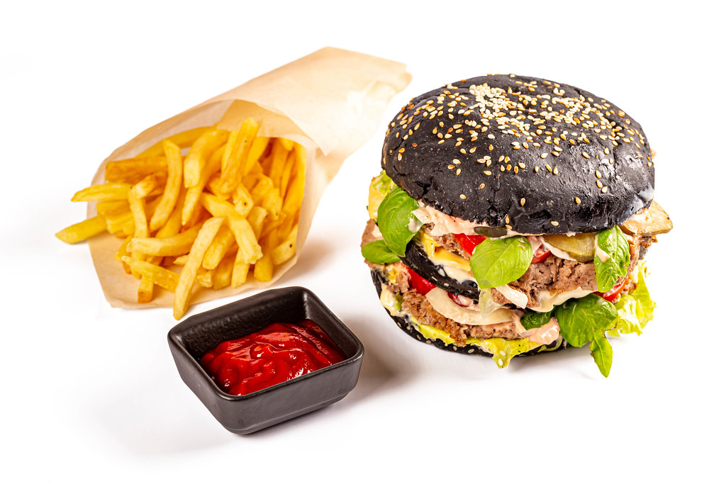 Fast food background with black burger and fries