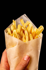 Close-up of french fries in a female hand on a black background