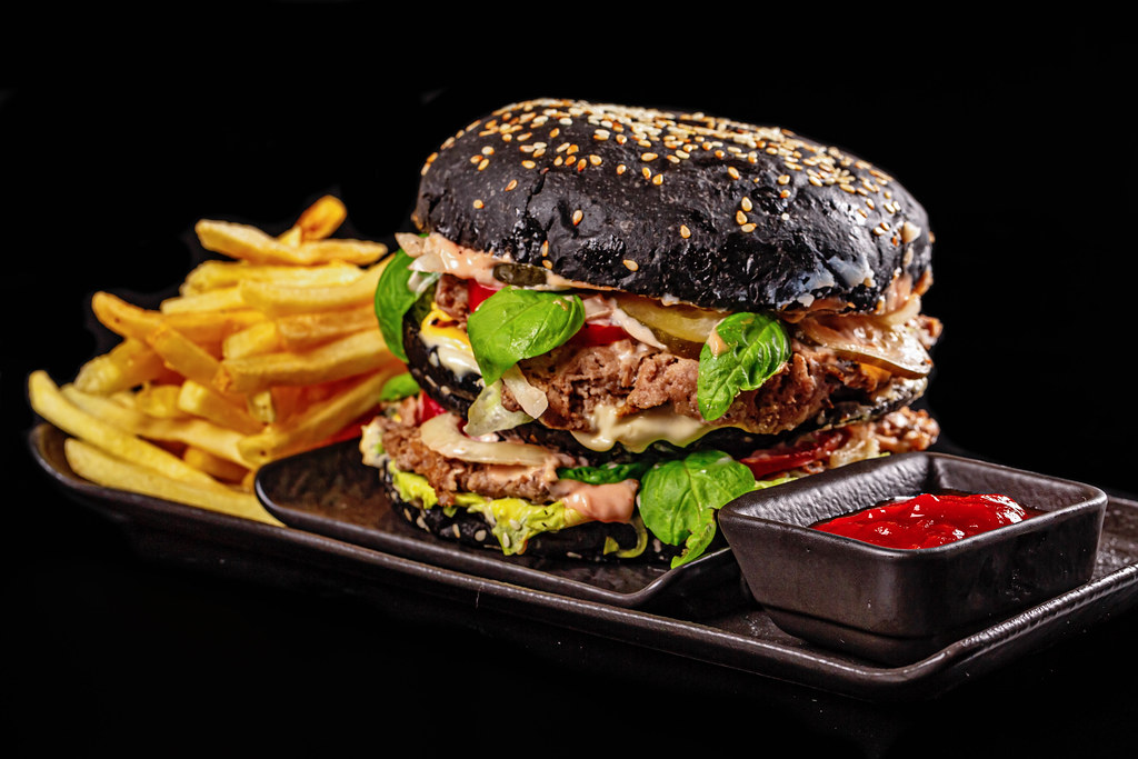 Fresh hamburger with black bun, cutlets, sauce and vegetables served with fries and ketchup