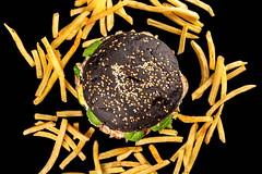 Top view of black burger and scattered fries on black