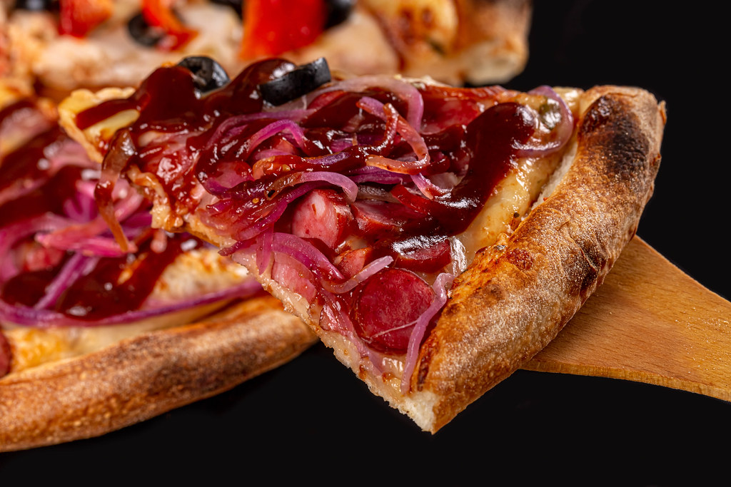 Close-up, slice of pizza with purple onion, smoked sausages and barbecue sauce