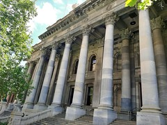 Adelaide. The western part of Parliament House built in Kapunda grey marble. Architect of this Greek design with  Corinthian columns was by Edmund Wright.  Completed in 1889. Eastern wing added 1939.