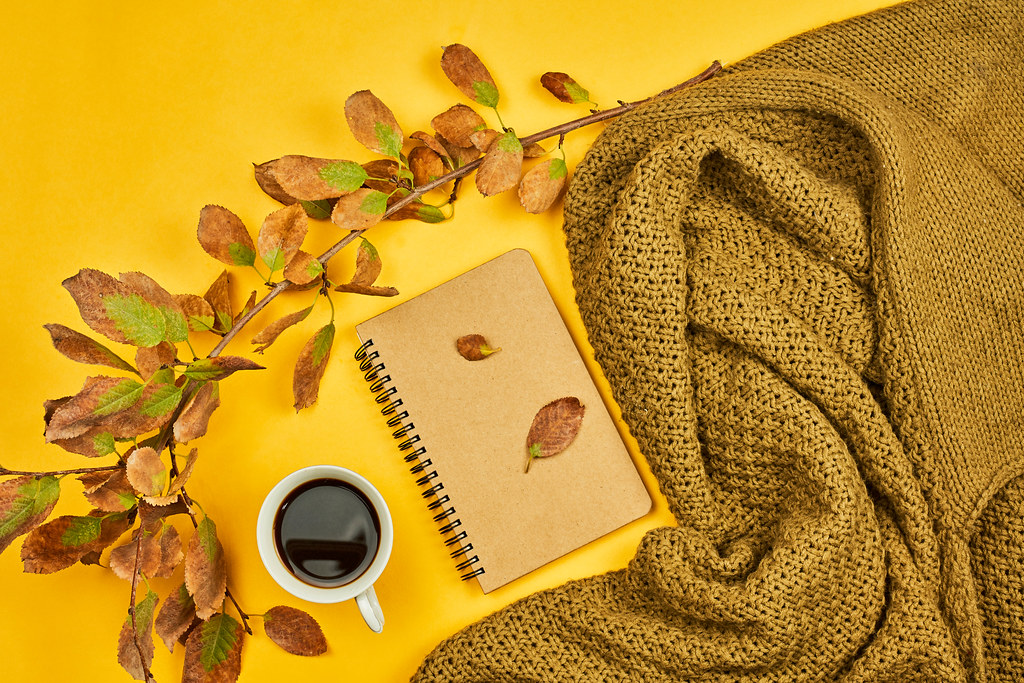 Cozy fall atmosphere with a cup of coffee, autumn leaves and warm sweater