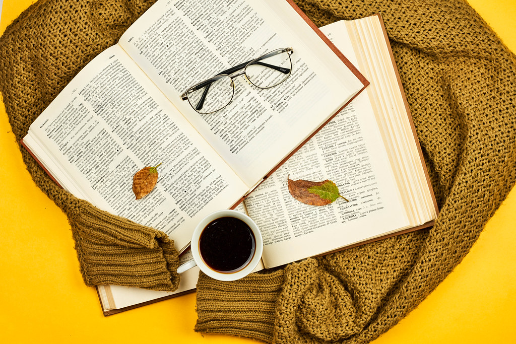 Overhead view of opened books on knitted sweater and coffee mug