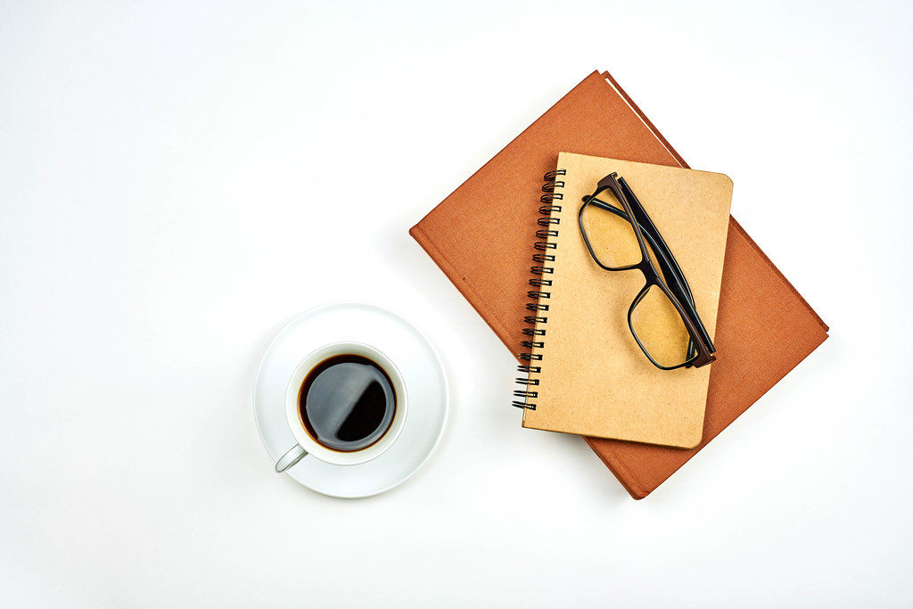Mug of coffee and two notepads on white background