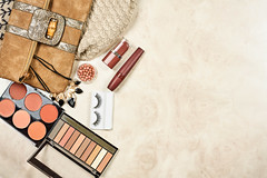 Cosmetic bag with make-up products on marble background
