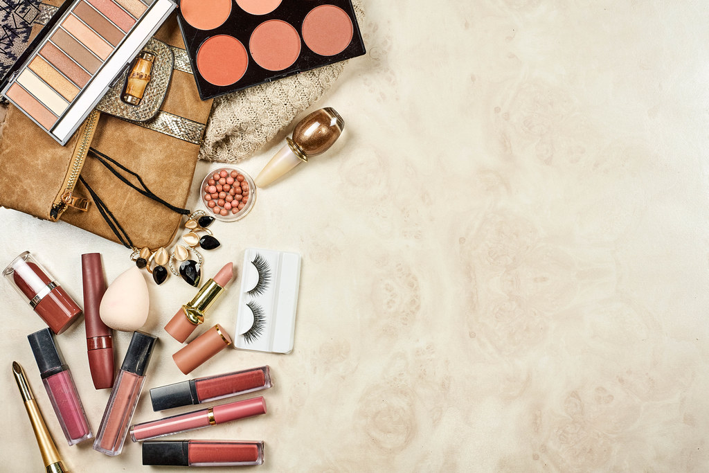 Flat lay image of professional make-up cosmetic products on pastel marble background