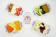 It's lunchtime. Alarm clock and food in lunchboxes