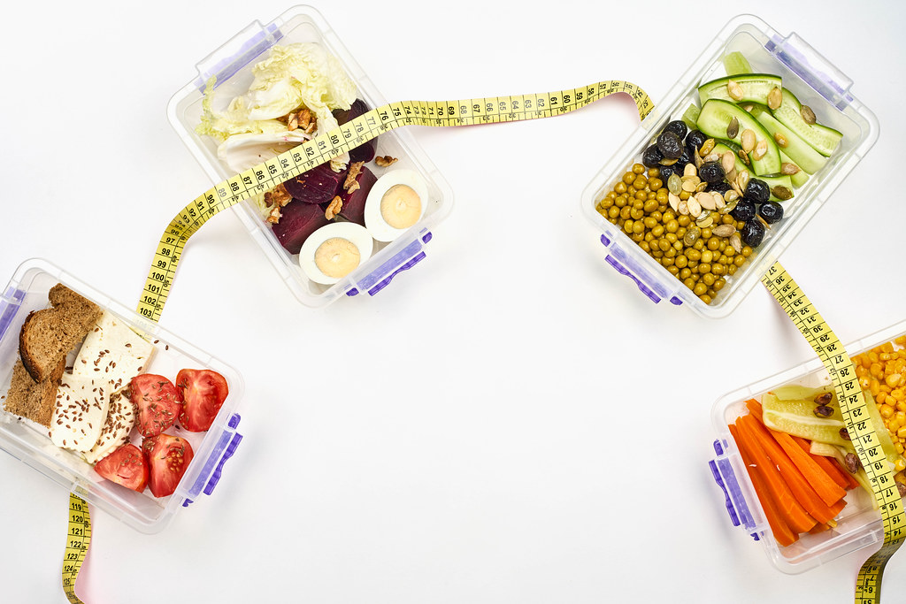 Vegetarian meals in plastic box connected with measuring tape