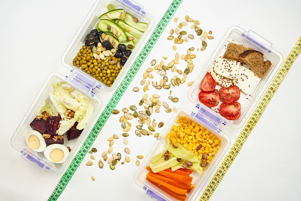 Flatlay image of healthy salads with fresh organic vegetables with measuring tapes on white