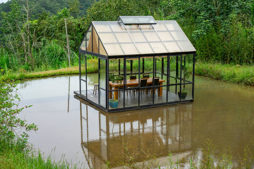 Tisch und Stühle in einem Glashaus in der Mitte eines Teiches in der Natur