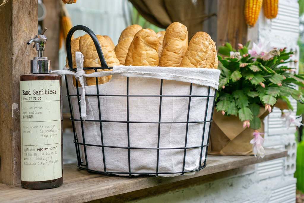 A Bottle of Hand Sanitizer next to a Basket with Baguettes