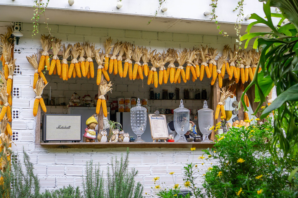 Front of a Cafe Bar with Corn on the Cob Decorations and many Flowers
