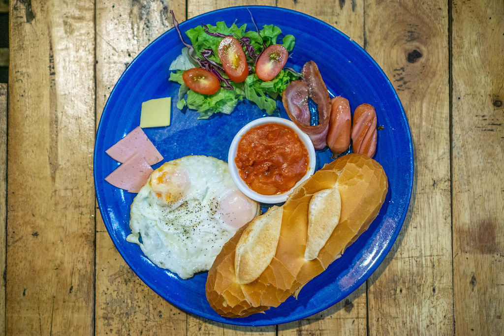 Top View Photo of Western Breakfast with Baguette, Sunny-Side Up Egg, Bacon, Sausage, Butter and Ham on a Blue Plate