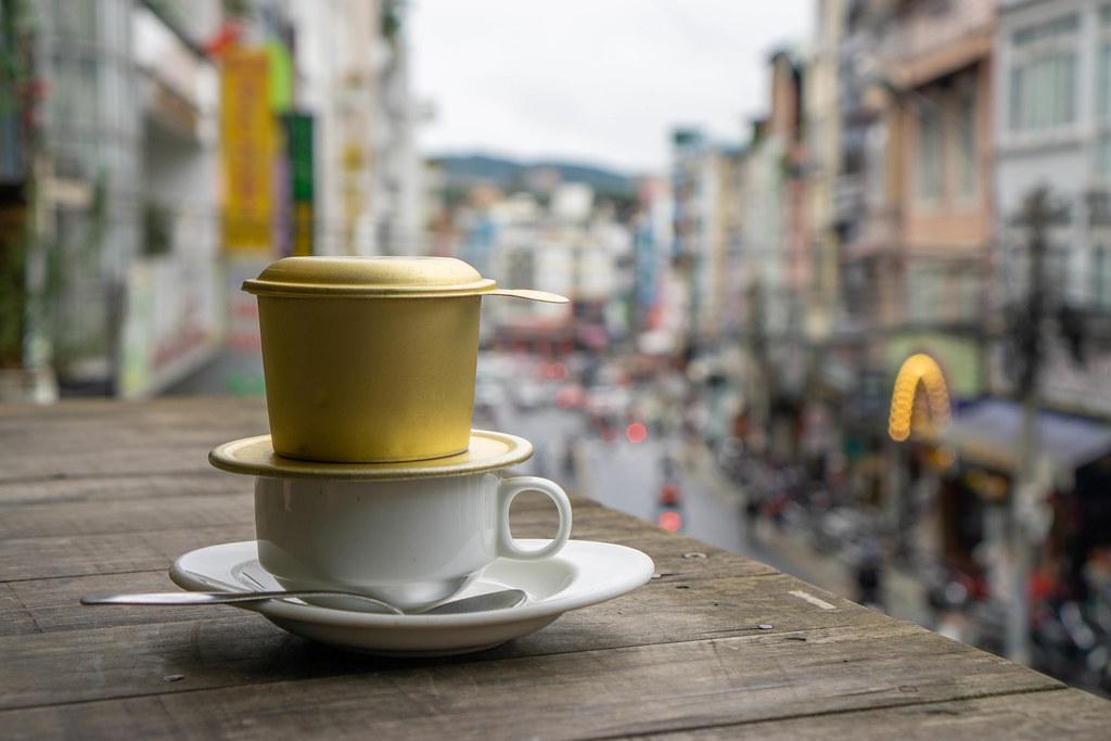Weiße Tasse mit Löffel und Untertasse mit Stadtblick im Hintergrund Nahaufnahme
