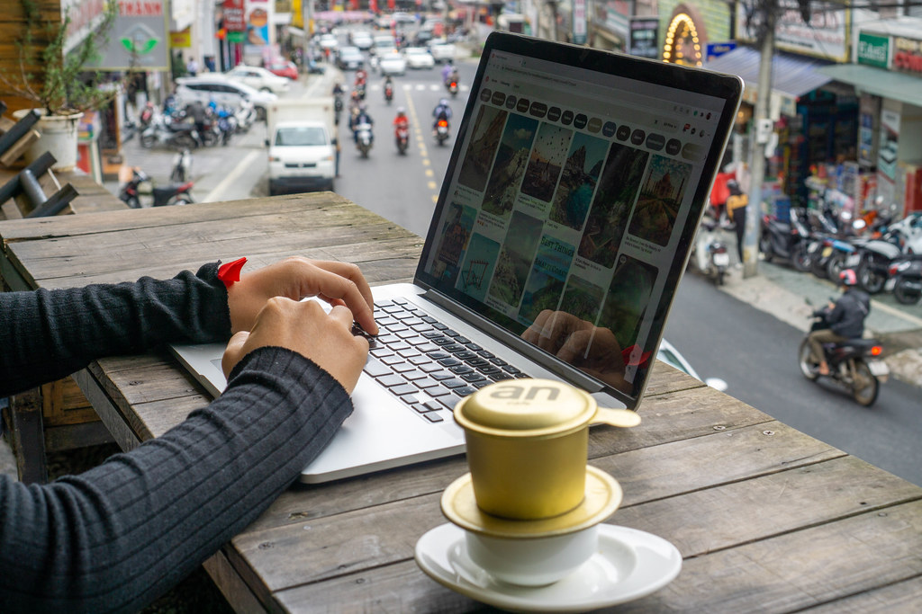 Person working online on a Laptop at a Cafe with Vietnamese Hot Coffee in Vietnam