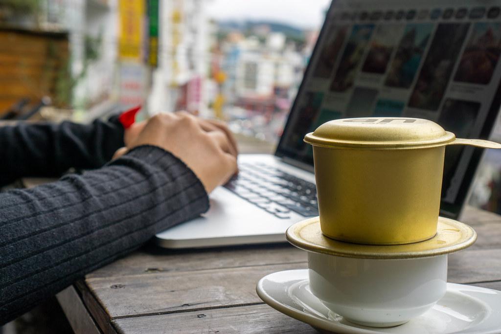 Person arbeitet online am Laptop mit Vietnamesischem Filterkaffee im Vordergrund Nahaufnahme