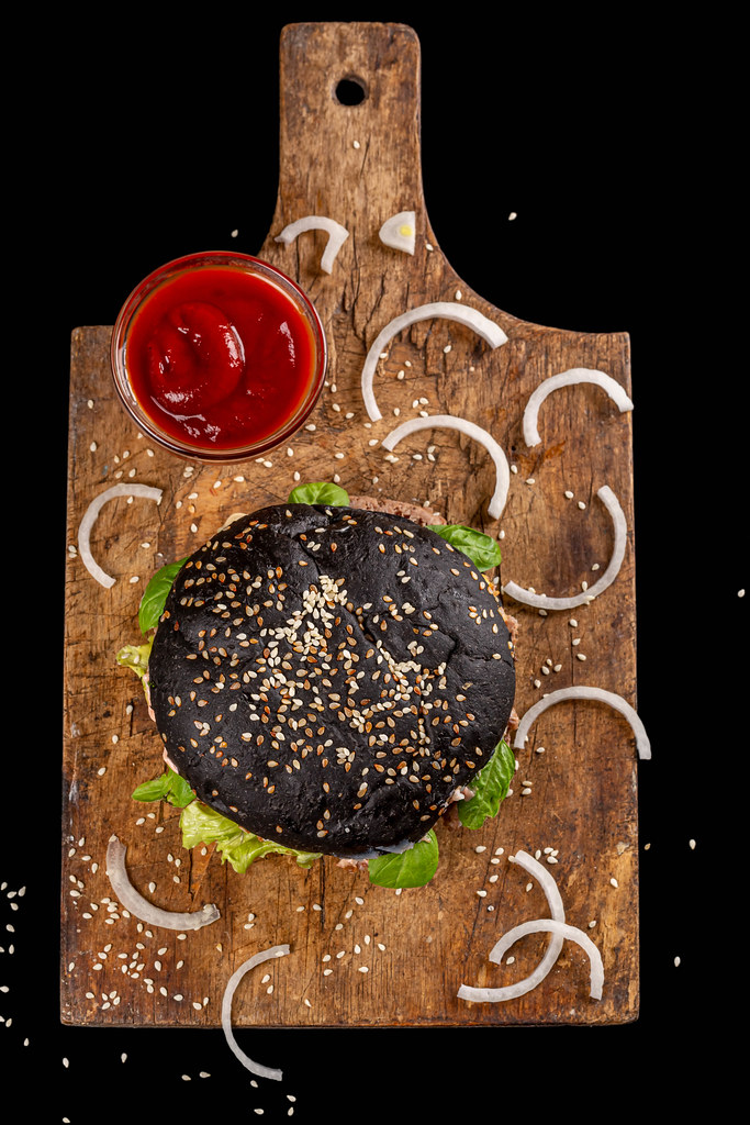 Black burger with cutlet, onion, sesame seeds and tomato sauce on an old wooden kitchen board, top view