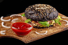 Gourmet black burger with spicy sauce on wooden board