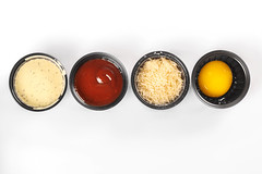 Set of sauces, grated parmesan cheese and egg yolk in black bowls, top view