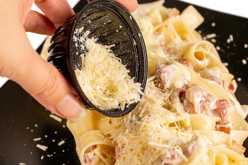 Close-up, pour grated parmesan cheese into carbonara paste