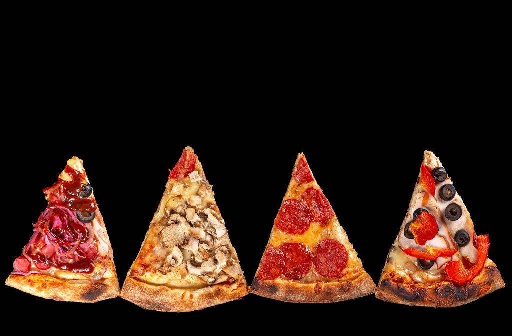 Four slices of pizza with different ingredients on a black background, top view