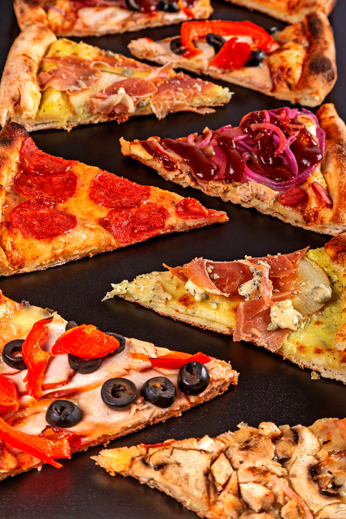Close-up, slices of different types of pizza. Fast food delicious background
