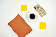 Drinking refreshing coffee at a bright workplace with a notebook, sticky notes, and smartphone