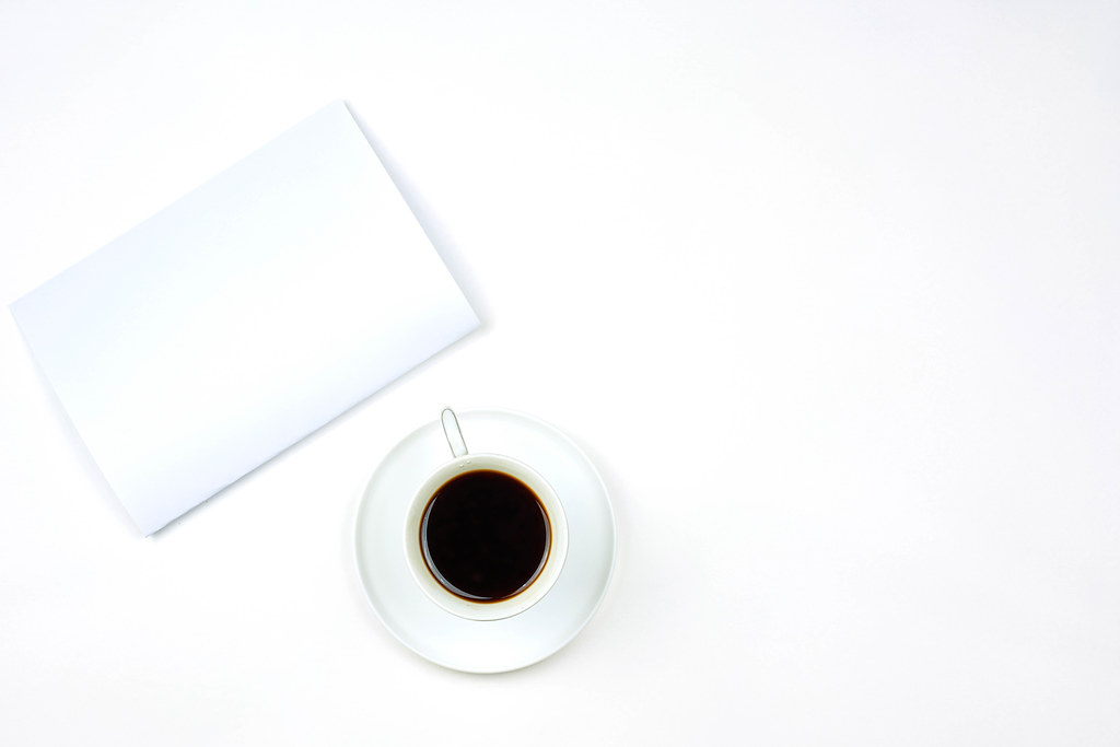 White business notepad with a cup of coffee on pure white background