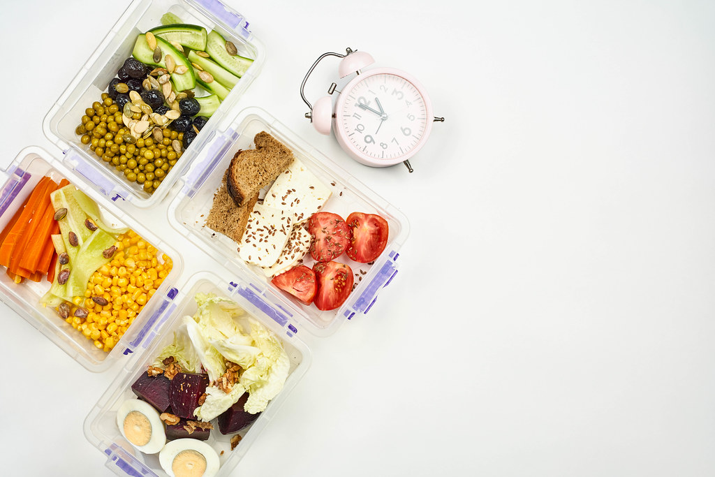 Flat lay arrangement of lunchboxes with organic meal and alarm clock showing lunchtime
