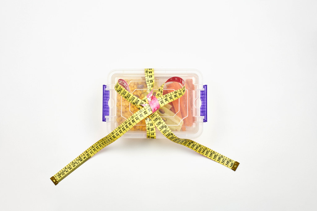 Lunchbox with dieting vegetarian food tied with measuring tape
