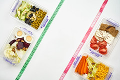 Vegetable salads in food containers and measuring tapes on white background