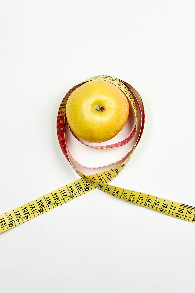 Apple and measuring tape on white. Dieting and healthy lifestyle concept