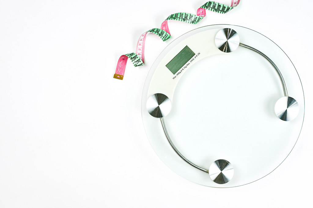 Weighting scales with a measuring tape on white background