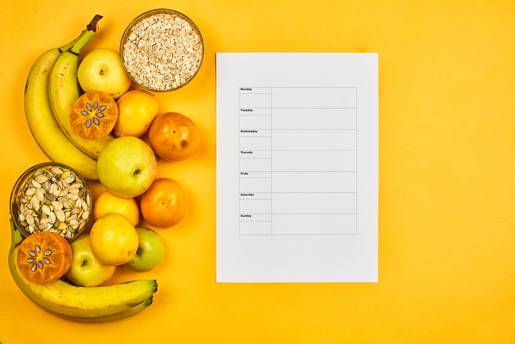 Healthy fruits, nuts and pumpkin seed with weekly meal planner on yellow