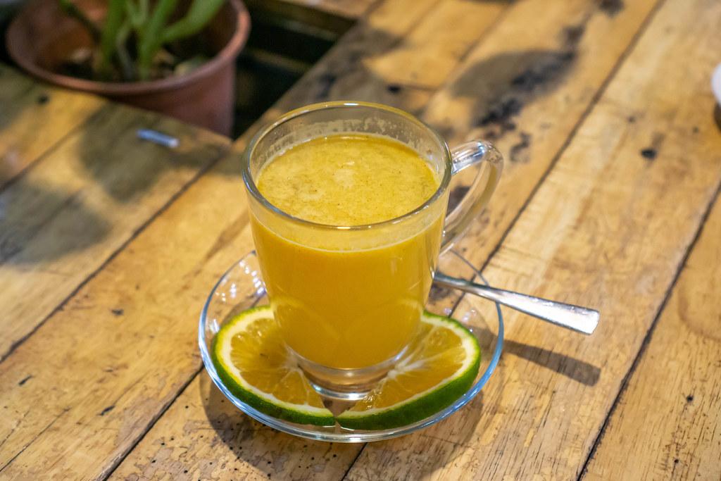 Heißer Orangen-Zimt Tee mit Orangenscheiben auf einem Holztisch