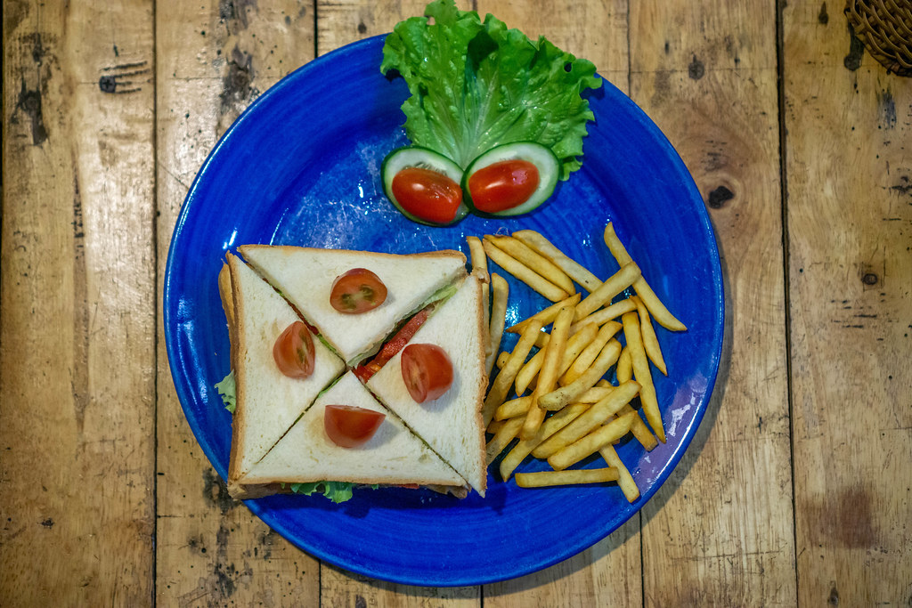 Top View Photo of Quartered Tuna Sandwich with French Fries and Cherry Tomatoes on a Wooden Table.