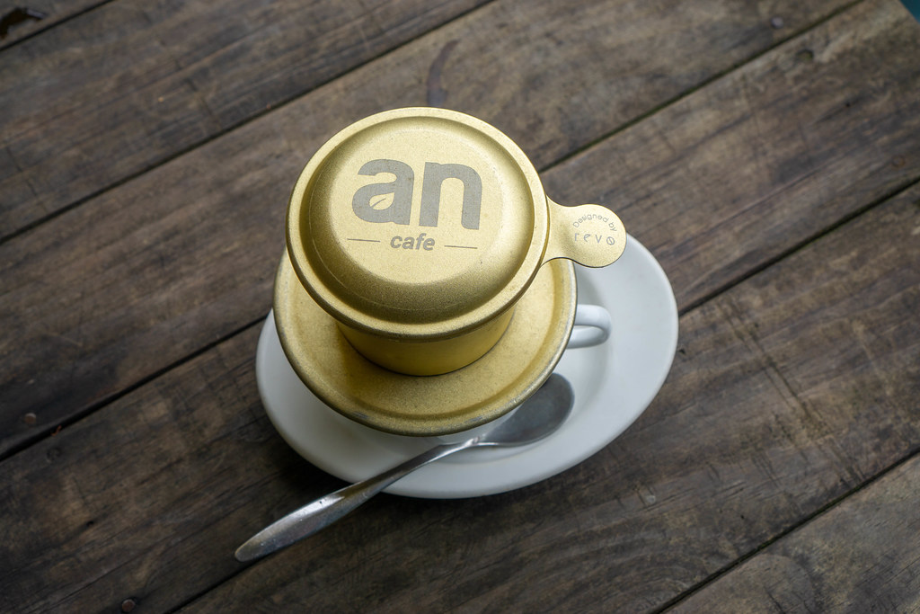 Top View Photo of Vietnamese Hot Coffee with Saucer and Spoon on a Wooden Table