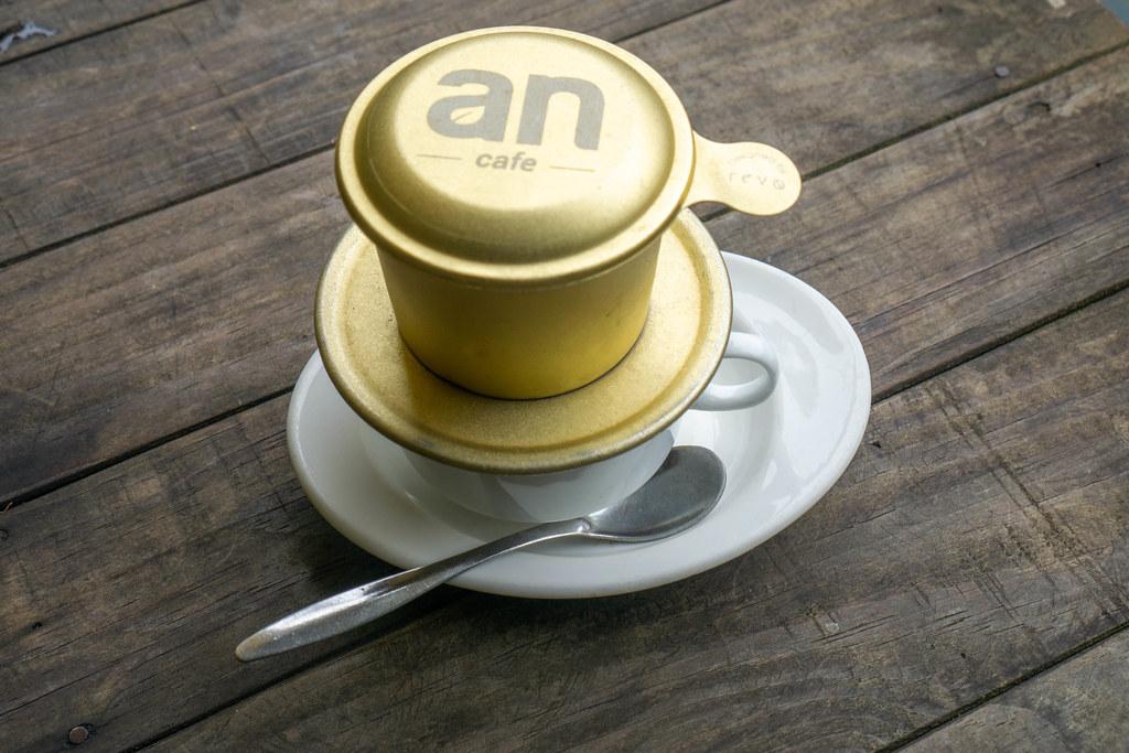 Vietnamesicher Kaffee mit Löffel und Untertasse auf einem Holztisch Draufsicht