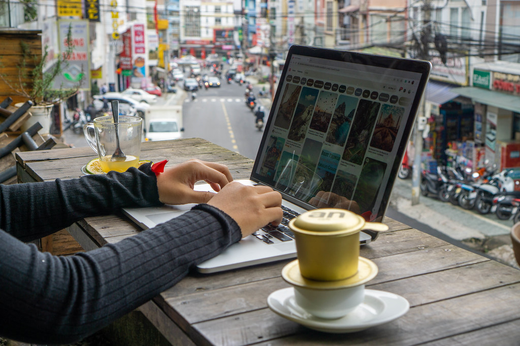 Digitaler Nomade arbeitet an einem Laptop mit Vietnamesischem Kaffee und Stadtblick